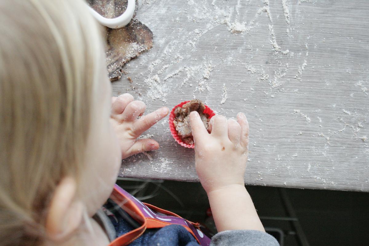 Schwofen vorm Ofen: Teig in die Pralinenförmchen manschen. Foto: Julia Marre
